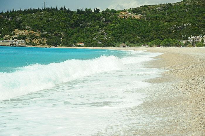 turkizno morje z belo peno na beli plaži