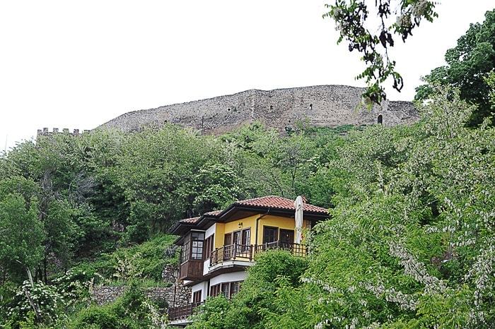 Tipična albanska arhitektura hiše in mogočno obzidje zadaj