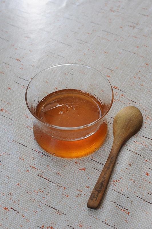 skodelica medu in lesena žlica poleg