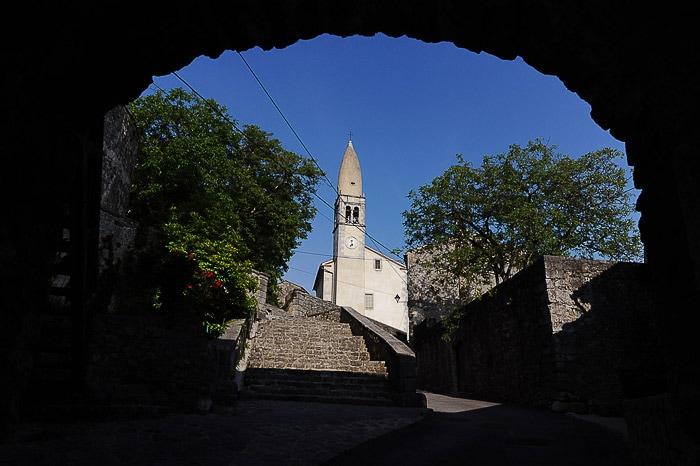 pogled skozi tunel na kamnito cerkev, vas Štanjel