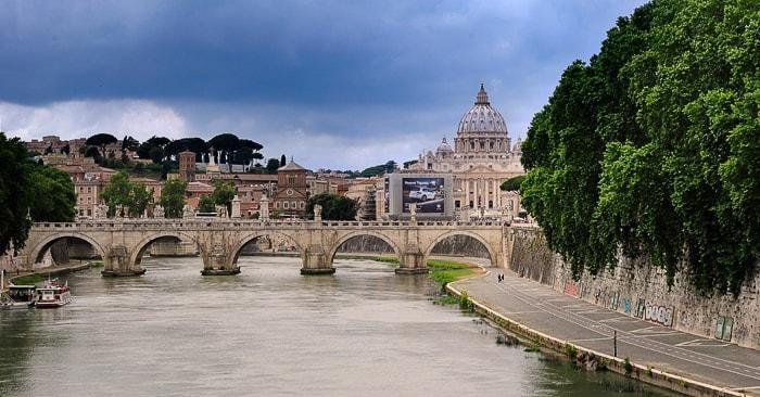 reka Tibera s kamnitim mostom in kupolo sv. Petra v ozadju
