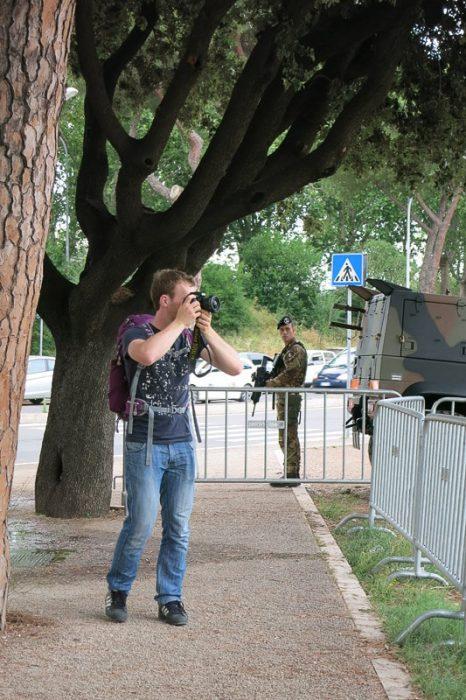 moški fotografira, v ozadju vojak s puško. Vatikan 2016