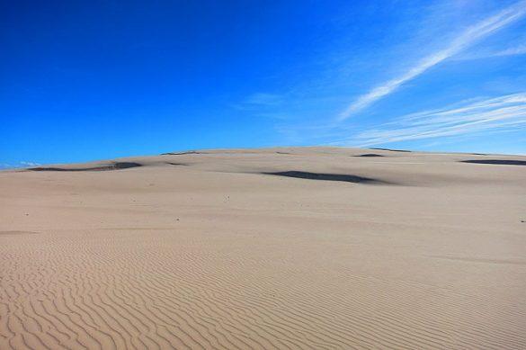 peščena sipina in modro nebo v ozadju