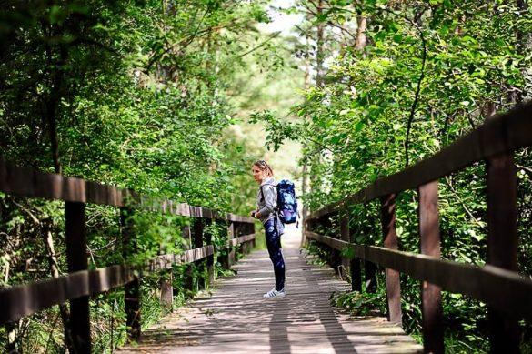 ženska z nahrbtnikom stoji na lesenem mostu sredi gozda