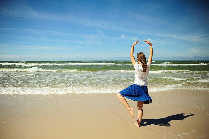 ženska izvaja baletno pozo na peščeni plaži