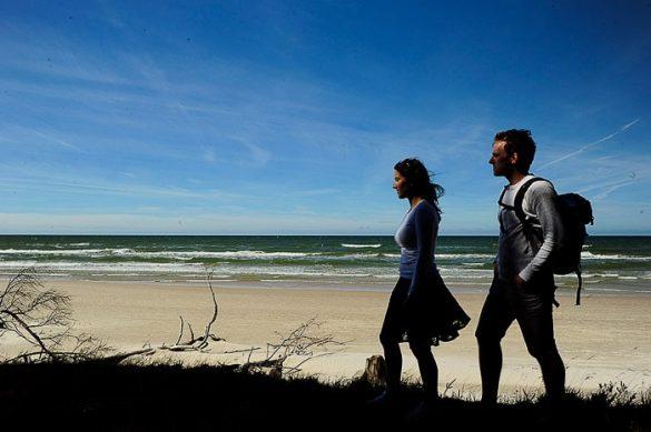 moški in ženska hodita po robu gozda, v ozadju peščena plaža in morje