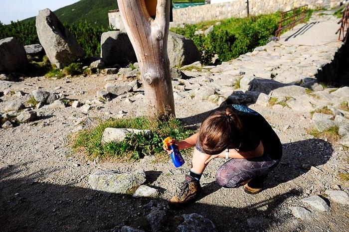 ženska v gorah se maže s sončno kremo