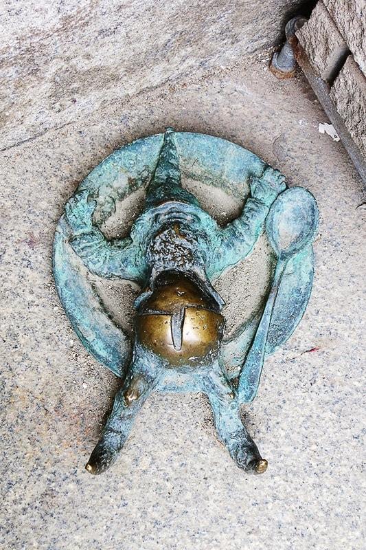 skulptura palčka, ki leži na tleh