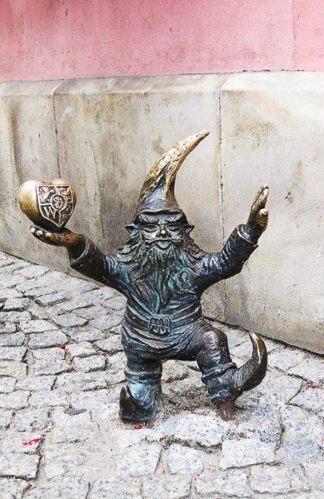 bakrena skulptura palčka, ki v eni roki drži srce
