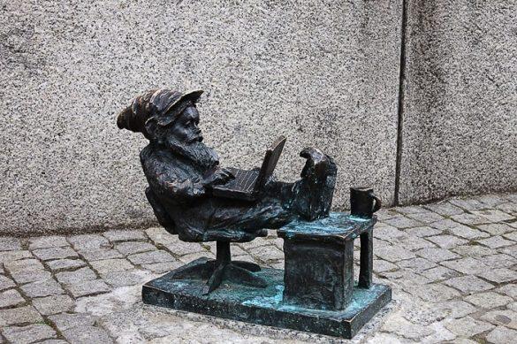 skuplptura palčka za mizo in z računalnikom na kolenih