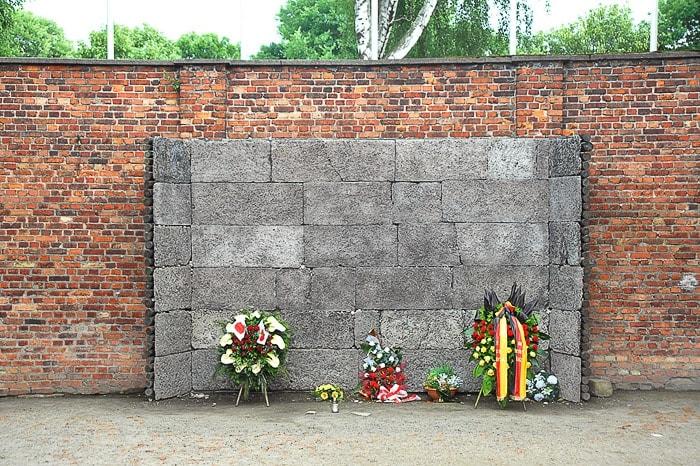 opečnati in betonski zid z venci in svečami. Nekoč so tu ubijali jude