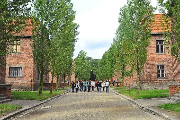 skupina turistov na makadamski cesti med opečnatimi barakami Auschwitz-a