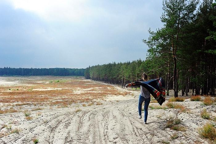 ženska hodi po mivkasti puščavi, ob strani so zelena drevesa