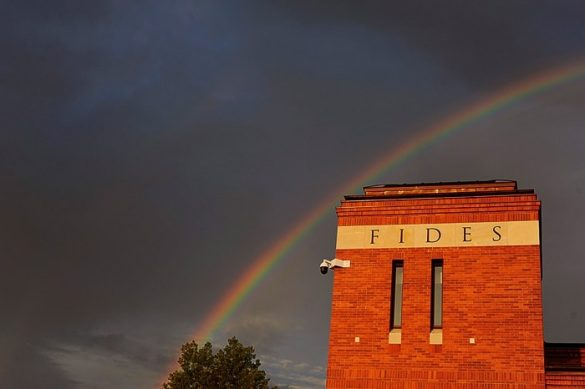 mavrica na temnem nebu, spredaj pa stavba z napisom Fides, vera