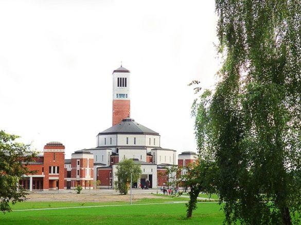 cerkev sv. janeza pavla II v Krakovu. 8-kotna cerkev z oranžnim, opečnatim stebrom med drevesi