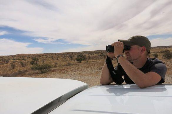 moški z daljnogledom na safariju