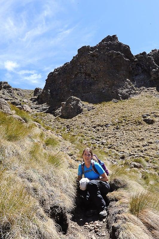 ženska sedi v travi pod goro