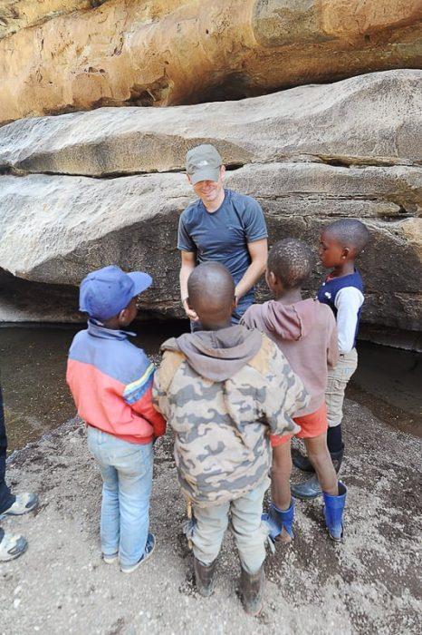 moški deli igrače črnskim otrokom, Lesoto.
