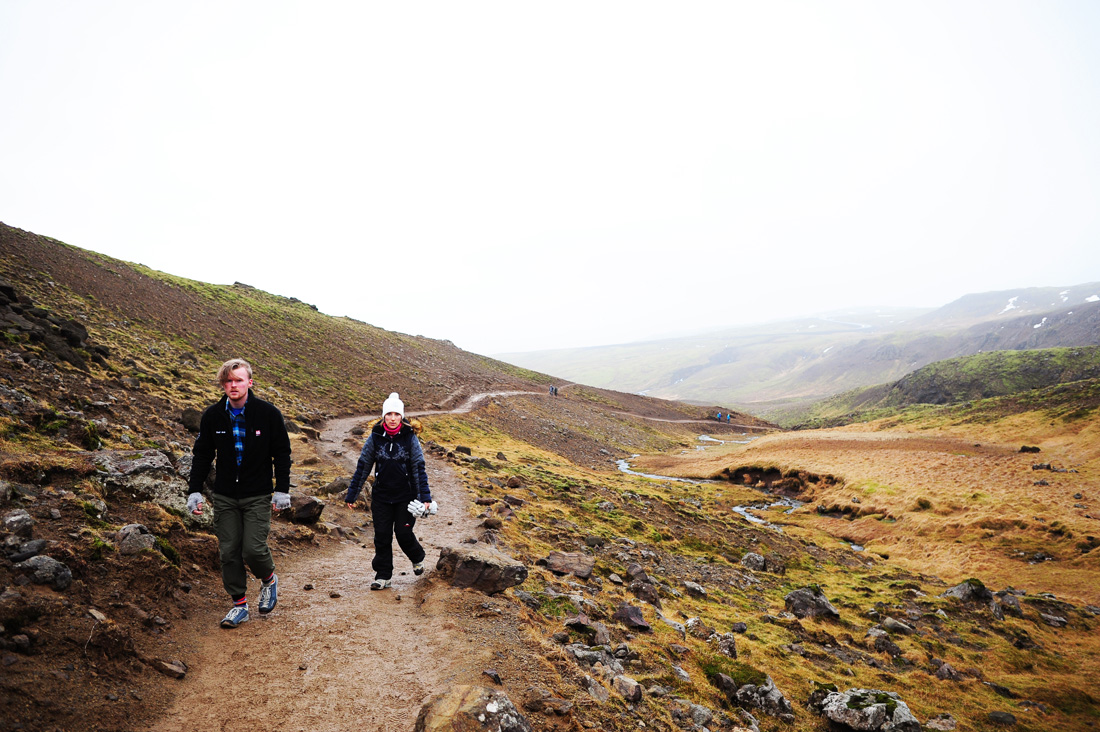 moški in ženska hodita po blatni gorski potki na Islandiji, dolina Reykjadalur