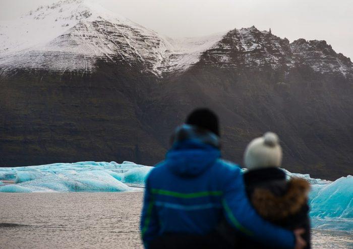 moški in ženska, objeta stojita pred ledenikom