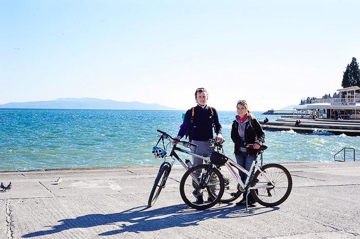 moški in ženska s kolesi na pomolu ob morju