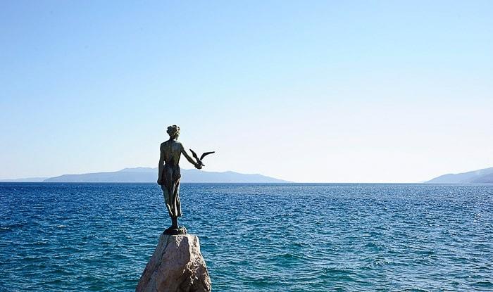 kip deklica z galebom nad morjem. Opatija