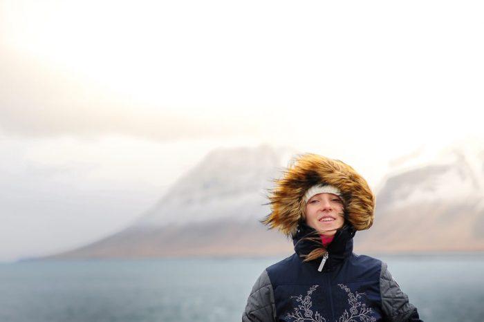 ženska s kapuco v močnem vetru