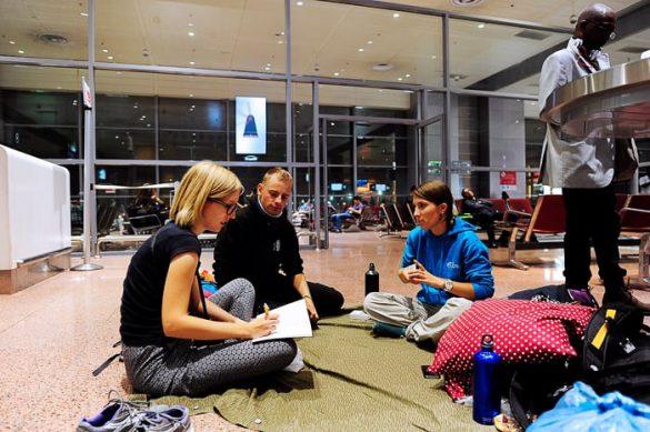 skupina popotnikov igra karte na letališču v Jeddah