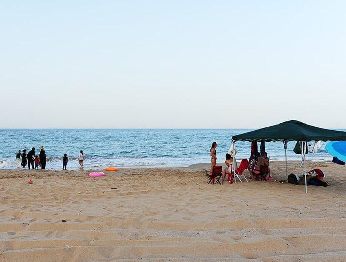muslimanske ženske v oblekah in zahodnjakinje v kopalkah na plaži. plaža Al Seifa, Oman