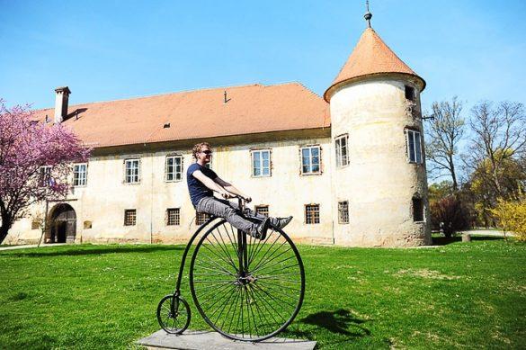 moški sedi na starinskem kolesu pred gradom