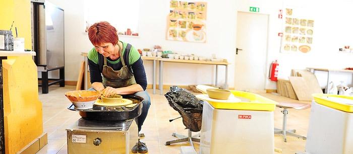 ženska oblikuje posodo iz gline