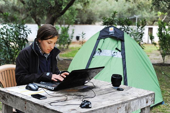 ženska sedi pri mizi v kampu (v ozadju je šotor) in tipka na računalnik