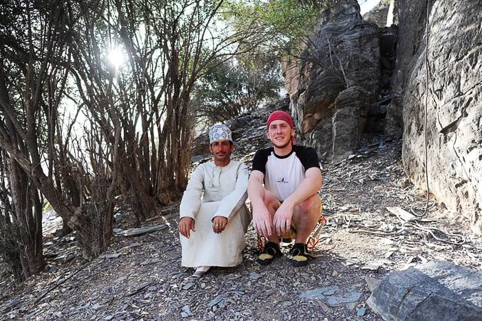 moški v omanski tradicionalni obleki in zahodnjaški moški v športni opravi sedita skupaj v plezališču Hadash
