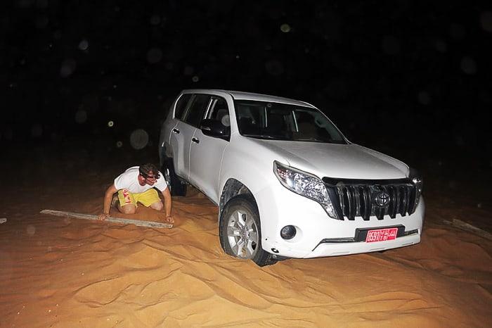 moški odkopava pesek izpod nasedlega avtomobila