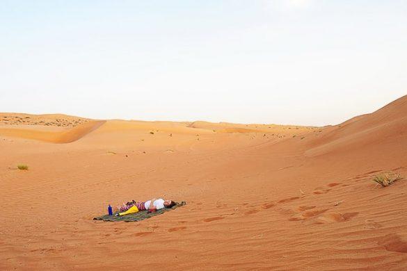Ženska leži na blazini v peščeni puščavi Wahiba