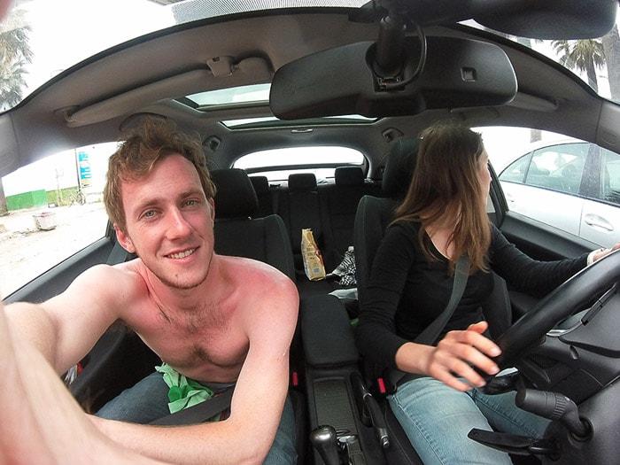 moški brez majice v avtu z opečenim hrbtom