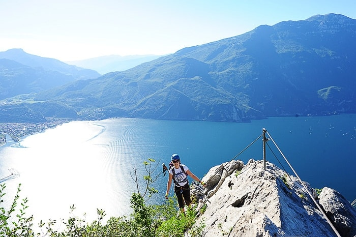 ženska se vzpenja na goro s pomočjo jeklenic, v ozadju Gardsko jezero