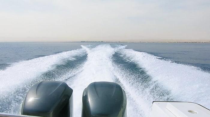 dva motorja motornega čolna in pogled po razpenjeni vodni gladini