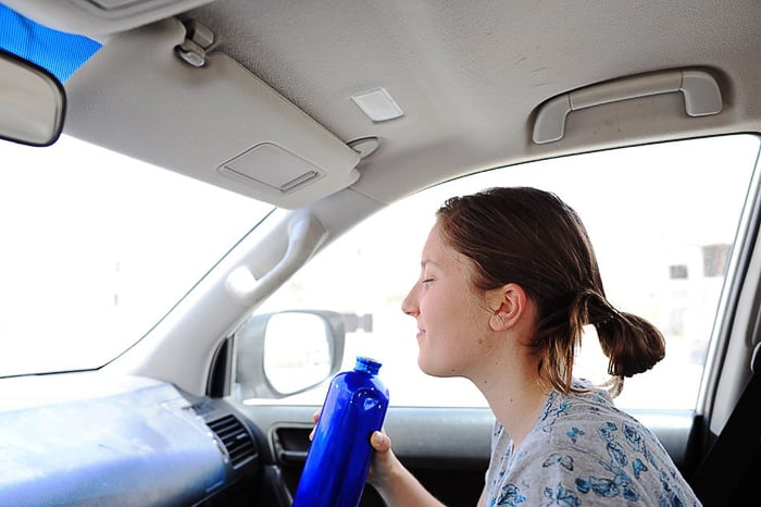 ženska z zaprtimi očmi in plastenko vode v roki sedi v avtomobilu