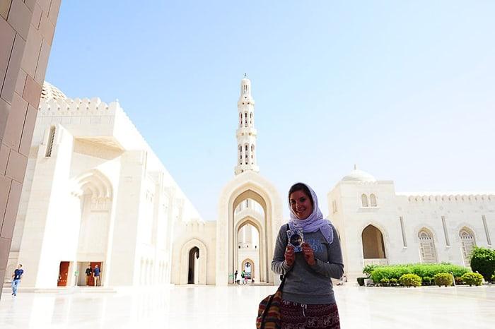 ženska s koranom v roki pred mošejo v Muškatu