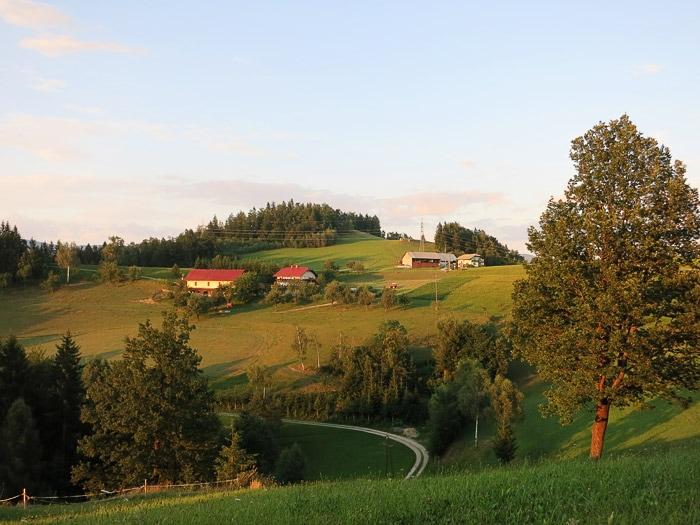 kmetija na griču, obsijana z večernim soncem