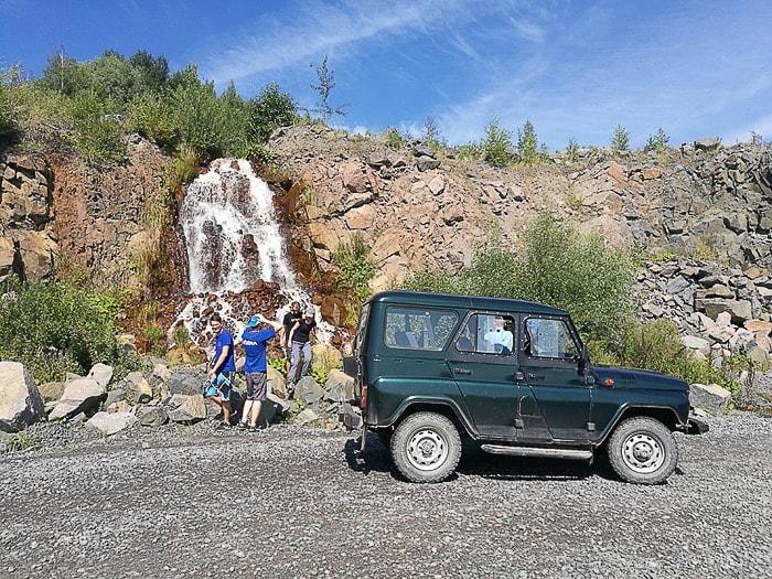 skupina ljudi poleg zelenega terenskega avta si ogleduje manjši slap