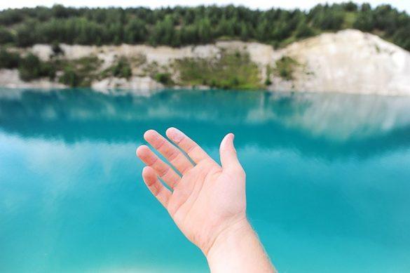 bel pesek na prstu roke, v ozadju turkizno modra voda, Beloruski Maldivi
