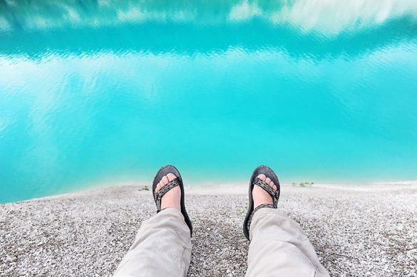 moške noge v Teva sandalih na beli peščeni plaži s turkizno modro vodo v ozadju