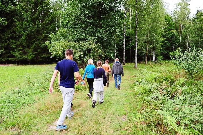 skupina ljudi hodi v vrsti po gozdni potki