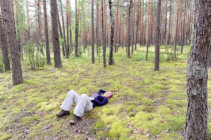 ženska leži na mahu sredi gozda Naliboki