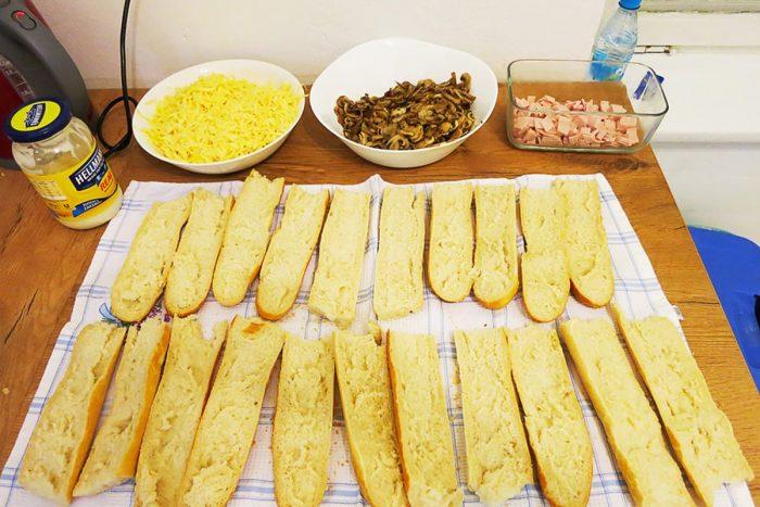 sestavine za zapiekanko: narezane baguete, sir v skodelici, kuhane gobe in šunka