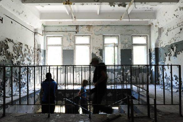 ljudje hodijo po zapuščeni in propadajoči stavbi Černobil 2