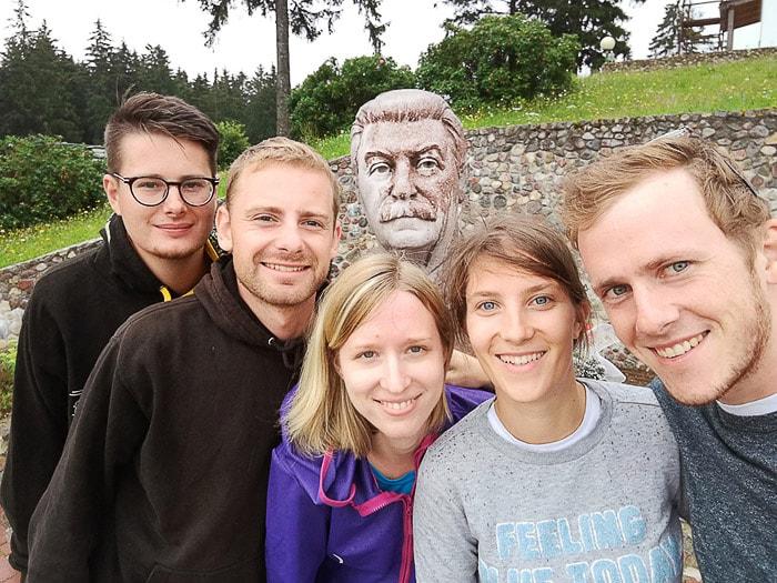 skupina mladih s kipom Stalina