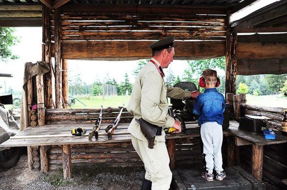 otrok strelja s puško, odrasel vojak mu pri tem pomaga